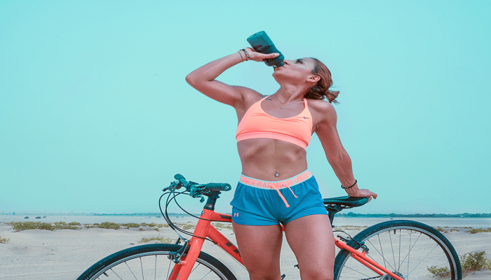 Jovem mulher bebendo água após pedalar, beba mais água para ter seu abdômen definido.