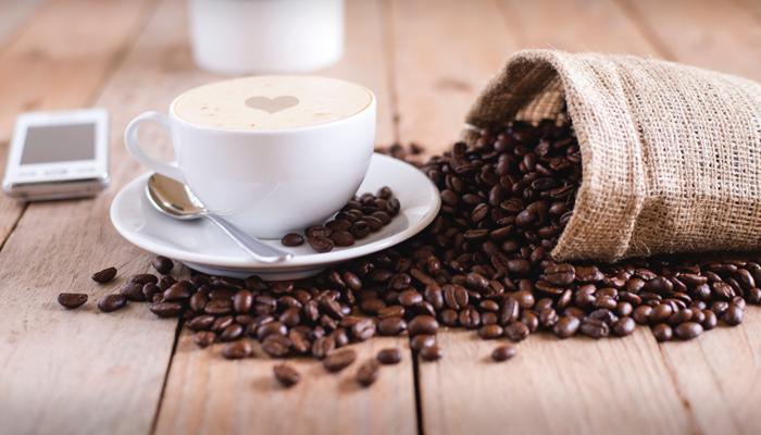 Café em uma xícara ao lado de um sementes de café sobre a mesa.