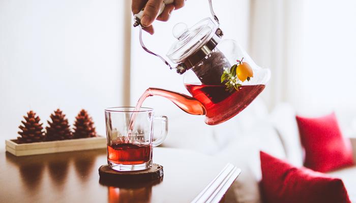Chá de hibisco pronto sendo despejado em um copo.