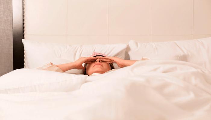 Mulher deitada na cama se preparando para dormir.