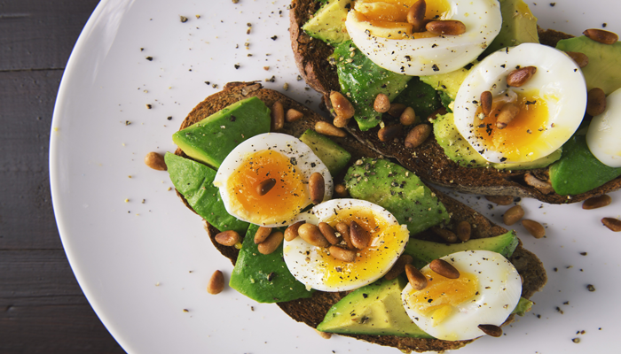 Ovos cozidos cortados ao meio servido em um prato redondo com oleaginosas e pão integral. Alimentos mais ricos em proteínas