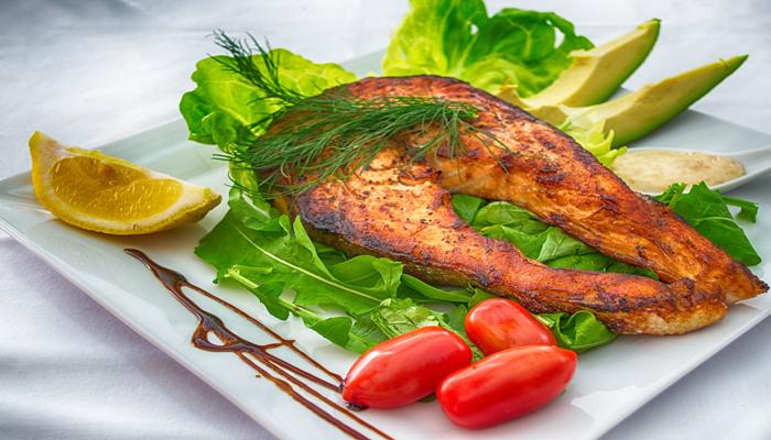 Prato quadrado com salmão grelhado, alface, pimenta e outros alimentos. Salmão é rico em proteínas, omega 3 e outros nutrientes importantes para o nosso corpo.