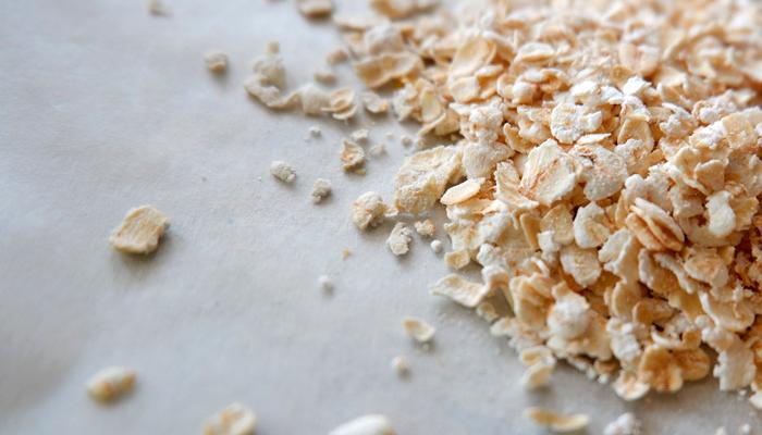 Aveia em flocos sobre a mesa. A aveia é uma excelente fonte de carboidratos e de fibras, promovendo maior saciedade.